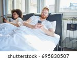 young couple lying in bed ... | Shutterstock . vector #695830507