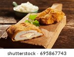 Small photo of Cordon bleu chicken with parsley served on wooden cutting board