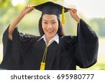 Small photo of Educational theme.Beautiful woman graduating smiling in an academic gown.