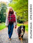 Stock photo woman walking the dog on leash in park on path covered with colorful fall foliage 696130843