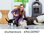 Stock photo woman with cute kittens and playing tunnel on floor in apartment 696130987