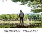 man standing on rocks edge the...   Shutterstock . vector #696261697