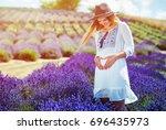 pregnant woman in white dress... | Shutterstock . vector #696435973