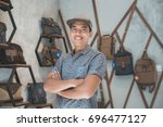shopkeeper at his bag store... | Shutterstock . vector #696477127