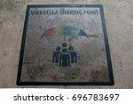 An Umbrella Sharing Floor Sign...