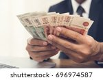 businessman counting money ... | Shutterstock . vector #696974587