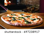spinach pizza served in a... | Shutterstock . vector #697238917