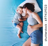 pregnant mother and son laying... | Shutterstock . vector #697419523