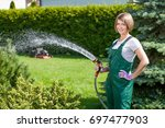 young woman watering in the... | Shutterstock . vector #697477903