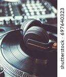 dj headphones on turntables... | Shutterstock . vector #697640323