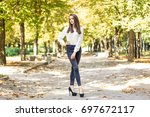 the girl is walking in the park   Shutterstock . vector #697672117