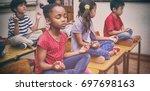 pupils meditating in lotus... | Shutterstock . vector #697698163