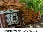 Small photo of Lifestyle still composition with medium format analog film camera Agfa Isola in original leather case and wicker basket with carrots inside, on wooden texture table. Natural warm summer sunlight.