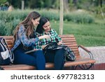 young girls sitting on wooden... | Shutterstock . vector #697782313