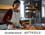smiling woman cutting zucchini... | Shutterstock . vector #697792513