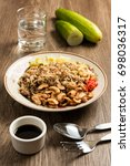 Small photo of Dish of chinese black olive fried rice with fork and spoon, altogether with glass of drinking water on table.