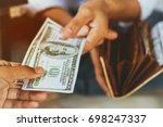 Small photo of people's hand with many US dollar banknotes giving to someone