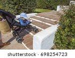 mother carries a stroller down... | Shutterstock . vector #698254723