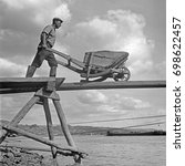 Small photo of Man walking with wheelbarrow on plank above water