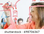 woman painting scheme on glass... | Shutterstock . vector #698706367