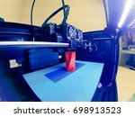 Small photo of 3D printer prints the form of molten plastic red close-up. Automatic three dimensional 3d printer performs plastic modeling in laboratory. Progressive modern additive technology