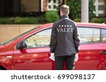 Small photo of Rear View Of A Valet Standing In Front Of Red Car
