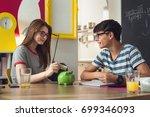 teenagers saving money in piggy ... | Shutterstock . vector #699346093