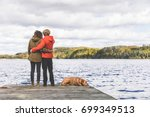 couple on the dock with a dog ... | Shutterstock . vector #699349513
