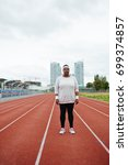 Small photo of Young plump woman in activewear standing on one of racetracks