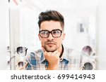 handsome young man choosing... | Shutterstock . vector #699414943
