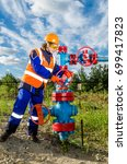 Small photo of Woman worker in the oilfield repairing wellhead wearing orange helmet and work clothes. Industrial site background. Oil and gas concept.