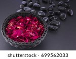 Stock photo spa red rose petals in a black basket and black pebbles 699562033