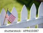 American Flag On White Picket...