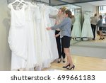 women looking at the white gowns | Shutterstock . vector #699661183