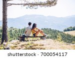 couple on mountain peak | Shutterstock . vector #700054117