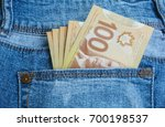 Small photo of Canadian banknotes are in the back pocket of blue jeans.