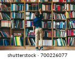 back view  boy stretches after... | Shutterstock . vector #700226077