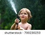 a little boy is playing outside ...   Shutterstock . vector #700230253