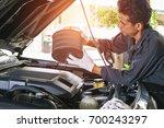 the technician removes the car... | Shutterstock . vector #700243297