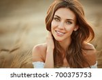 Stock photo portrait of a beautiful girl in a white dress in a field with ears at sunset in summer close up 700375753