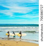 group of surfers going to surf... | Shutterstock . vector #700380727