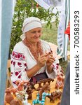 Small photo of ADYGEA, RUSSIA - AUGUST 19, 2017: cheerful woman in the shop with clay Souvenirs and toys at the festival of cheese Adyghe in Adygea