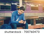 smart asian man holding mobile... | Shutterstock . vector #700760473