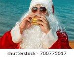 santa claus on the beach eating ... | Shutterstock . vector #700775017