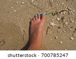 the foot standing on the beach... | Shutterstock . vector #700785247