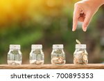 Small photo of Woman's hand saves a coin in the bottle put on the wood in the morning sunlight, Business investment and saving growth money concept.