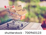 Small photo of Online shopping and delivery service concept. Paper cartons in a shopping cart on a laptop keyboard, this image implies online shopping that customer order things from retailer sites via the internet.