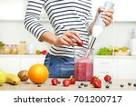 young woman cooking smoothie in ... | Shutterstock . vector #701200717