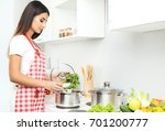 beautiful young woman cooking... | Shutterstock . vector #701200777