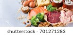 Small photo of Assortment of healthy protein source and body building food. Meat beef salmon chicken breast eggs dairy products cheese yogurt beans artichokes broccoli nuts oat meal. Copy space background